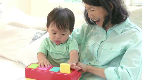 Grandmother And Grandson Playing With Toy Together Footage