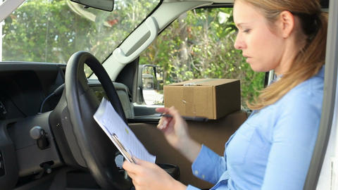 Female Delivery Driver Sitting In Van Filling Out Paperwork Live Action
