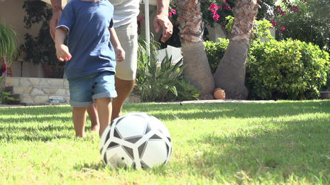 Grandfather Playing Football With Grandson In Garden Footage