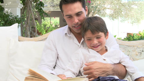 Father And Son Sitting In Garden Reading Book Together Footage