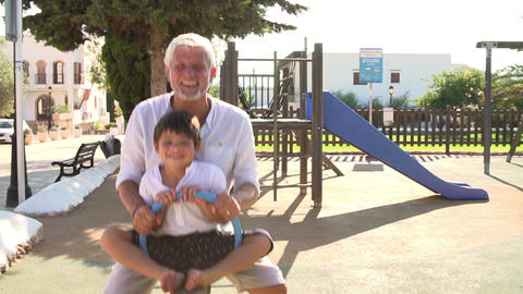 Grandfather And Grandson On Seesaw In Playground Footage