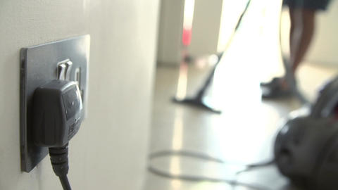 Close Up Of Plug Socket With Person Vacuuming In Background Footage