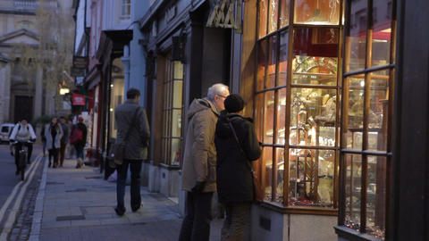 Senior Couple Looking In Antique Shop Window At Dusk Footage