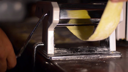 Housewife uses noodle making machine for making noodles. The dough for noodles,  Footage