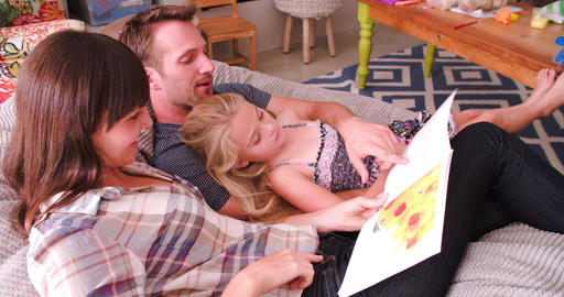 Parents Relaxing In Chair Reading Book To Daughter Footage