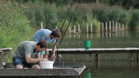 Fisherman baiting hook on fishing rod at lake Footage
