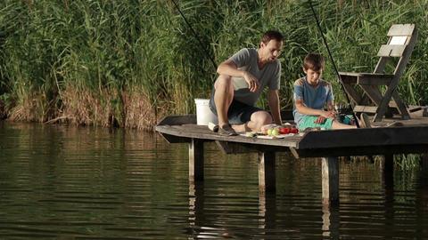 Fishermen having breakfast on wooden pier at pond Footage