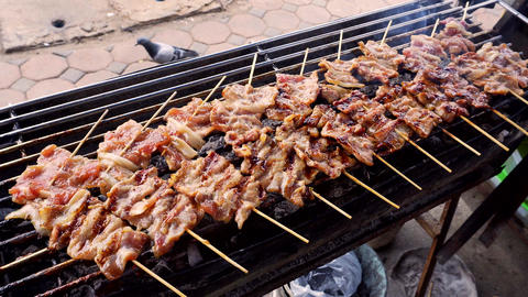 Thai style Grilled pork with skewer on charcoal griller for everyday meal Footage