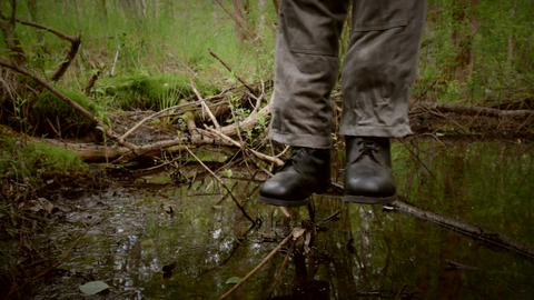 Hanged man in boots over the rotten swamp Footage