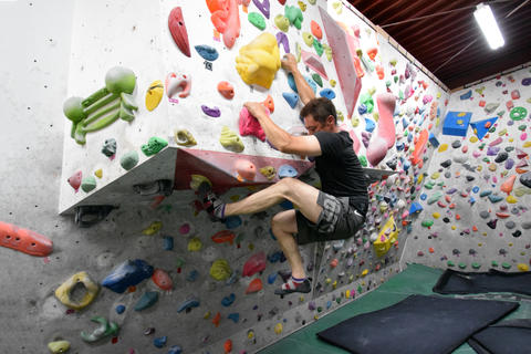 A Japanese man and girl is climbing on practice wall indoors Foto