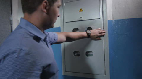 Backside View Man Comes to Switchboard and Shows Modern Meters Footage