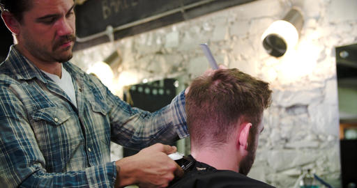 Male Barber Giving Client Haircut In Shop Footage
