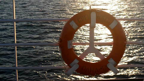Red lifebuoy on a boat crossing the sea at sunset Image