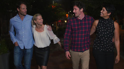 Group Of Mature Friends Walking Along Street On Night Out Footage