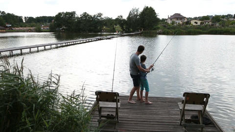 Father and son angling at tranquil lake in summer Live Action