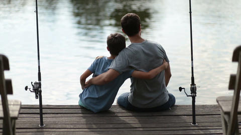 Affectionate father embracing son as they fish Footage