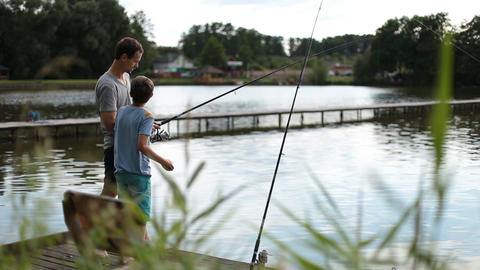 Positive dad and son with rod angling at pond Footage