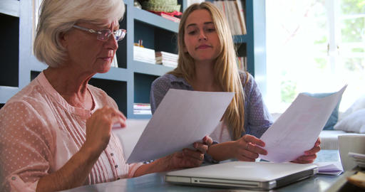 Daughter Helping Senior Mother With Paperwork In Home Office Footage