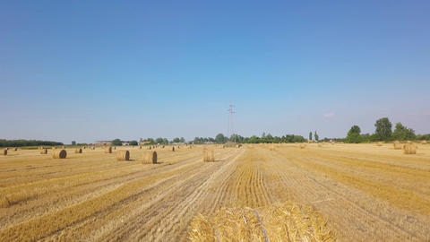 Clouds above field with rolls of hay at summer sunny day. Aerial view Footage