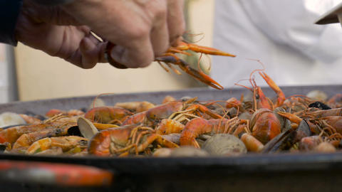 Close up of hands arranging shrimp in their shells in a paella pan Footage