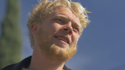 A millennial blond haired bearded man smiling against the blue sky - room for te Footage