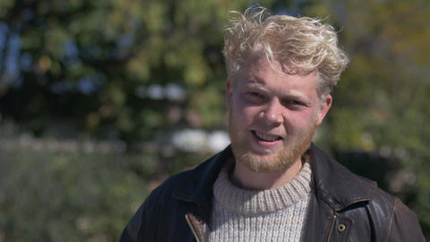 A handsome blond haired millennial man with a beard smiling and squinting in the Footage
