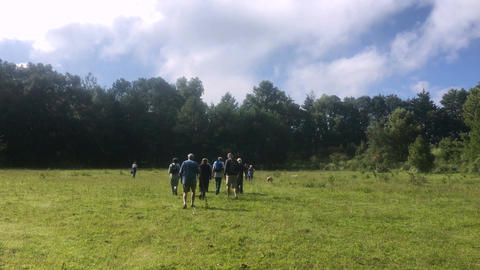 A group of hikers walk in a field towards the woods away from the camera with a  Footage