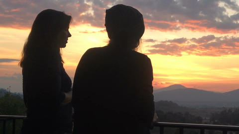 Silhouettes of two women talking overlooking a colorful sunset in the mountains  Footage