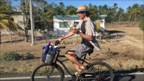 A middle aged man biking on a beach cruiser bicycle holding a glass of wine whil Footage