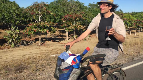 A man riding a bicycle cheers to the camera with a glass of red wine on a desert Footage