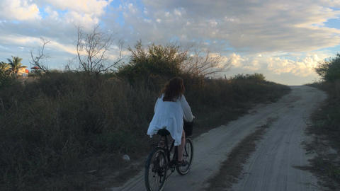 A blond woman in a white shirt rides a beach bike on the sand towards the sunset Footage