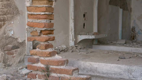 Dolly of an abandoned hotel room with bricks and crumbled tiles damaged in an ea Footage