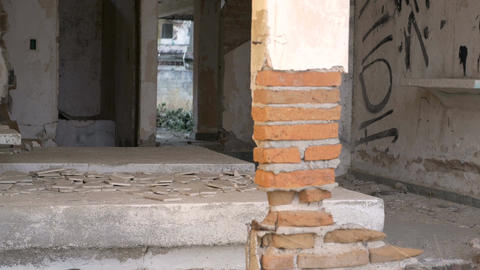 A pillar of bricks balance in a crumbling abandon building with broken tiles on  Footage