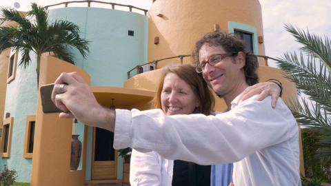 A married couple take a selfie and look at the photo in front of their colorful  Footage