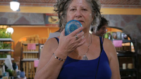 A older woman cools herself off with a portable fan in the summer while two peop Live Action