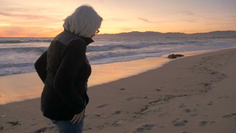 An attractive active mature woman talking and walking on beach at sunset in slow Footage