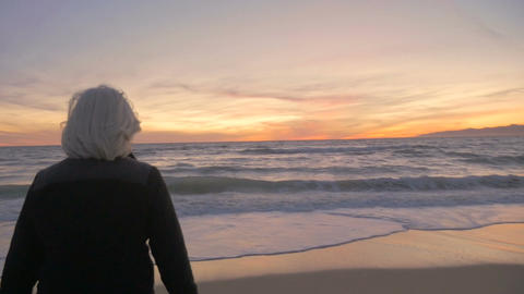 Healthy retired 60s mature active woman looking at a beautiful sunset on beach Footage