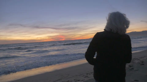 Retired healthy mature active 60s couple hugging and looking at sunset on beach. Footage