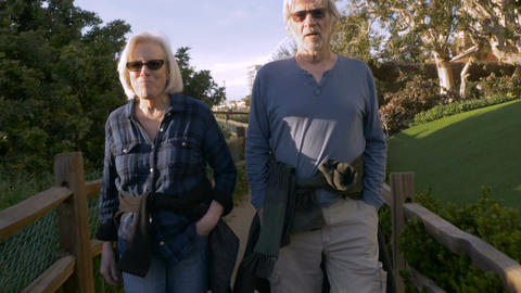 A happy active mature 60s couple walking outdoors on urban greenway. Retired hus Footage