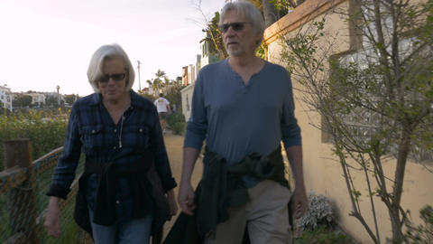 Active healthy happy attractive mature 60s adults walking in upscale neighborhoo Footage