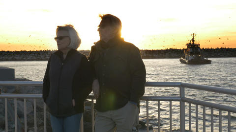 Happy retired couple enjoying ocean vacation in fall or winter during sunset wit Footage