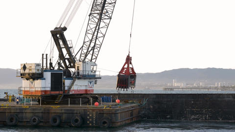 Dredger ship digging sand out of ocean floor on to a barge Footage