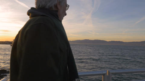 Handsome happy retired caucasian man enjoying sunset with sailboat on ocean behi Footage