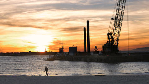Silhouette of a man in a hoodie walking on beach at sunset with dredger boat cra Footage