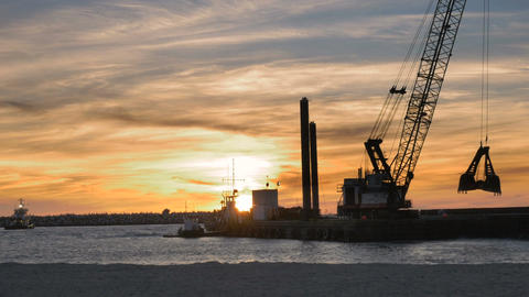 Dredger ship working at sunset with birds flying in background to control beach  Footage