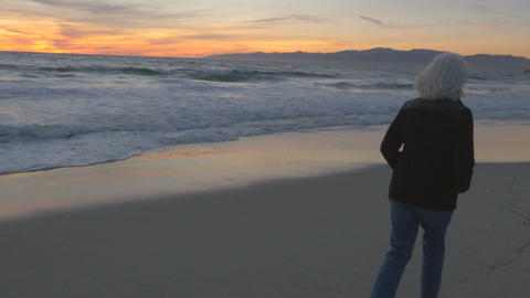 Single mature 60s woman with gray hair walking along beach at sunset. Fit health Footage