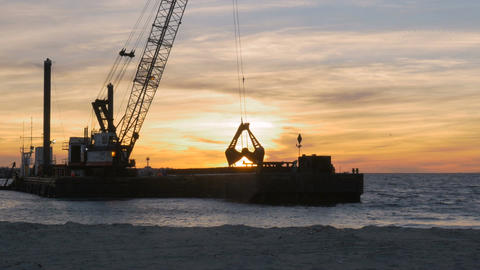 Dredger ship removing sand from ocean bottom at sunset to control beach erosion  Footage
