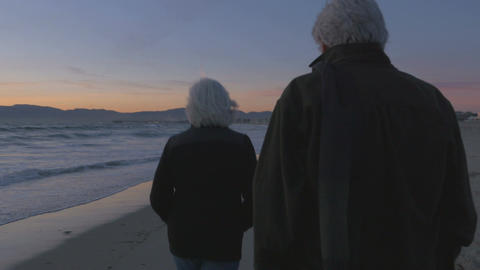 Happy elderly 60s couple walking and pointing along upscale beachfront at sunset Footage