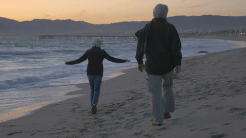 Happy mature 60s couple running and playing along upscale beachfront at sunset.  Footage