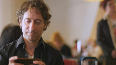 Handsome 30s man playing video game app on horizontal cell phone technology in a Footage